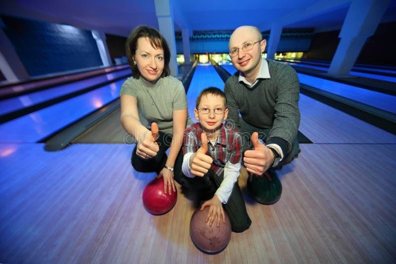 Familj i bowlingklubba och showshänder av oken arkivbild