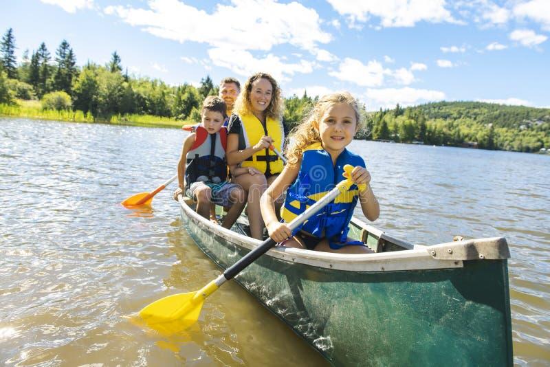 Familj i en kanot på en sjö som har gyckel royaltyfri fotografi