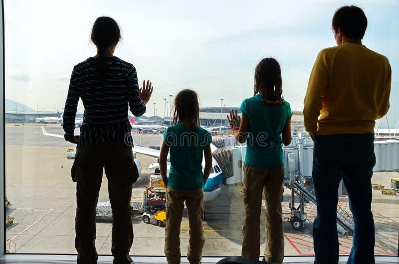 Familj i flygplatsen, loppbegrepp, konturer av föräldrar med ungar i slutligt väntande på flyg royaltyfri foto