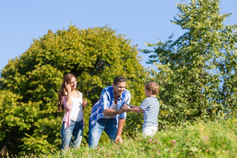 Familj i gräs på äng royaltyfri bild