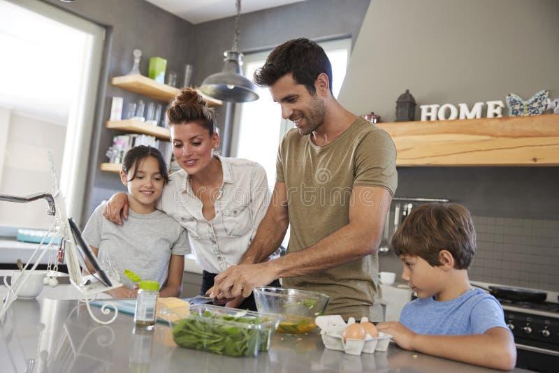 Familj i kök efter recept på den Digital minnestavlan tillsammans royaltyfri bild