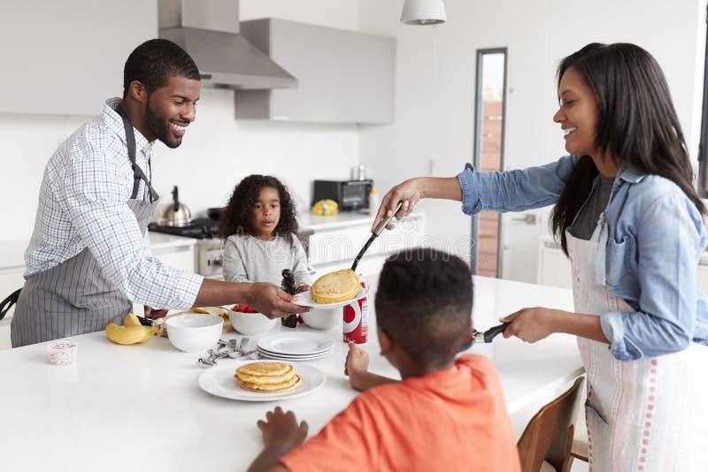 Familj i kök hemma som tillsammans gör pannkakor royaltyfria bilder