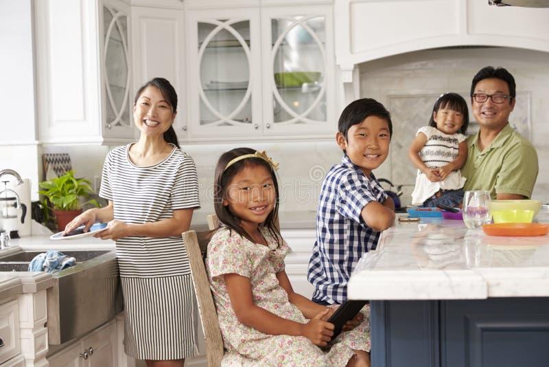 Familj i kök som gör sysslor och använder Digital apparater royaltyfri foto