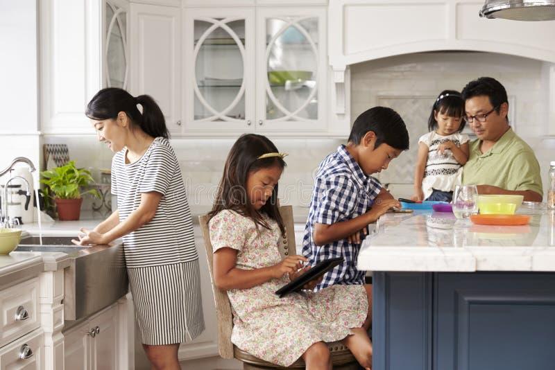 Familj i kök som gör sysslor och använder Digital apparater arkivbild