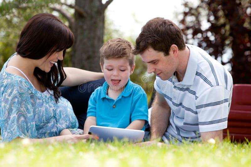 Familj i Park med den Digital tableten royaltyfri bild