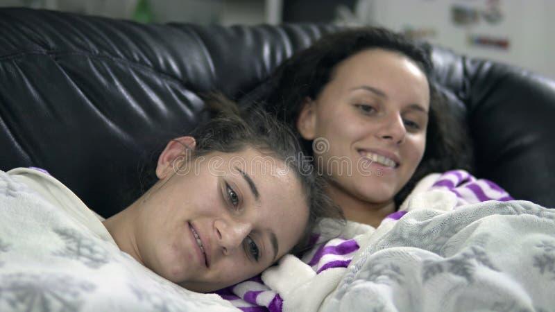 Familj i pijamas som skrattar, medan hålla ögonen på television royaltyfri fotografi
