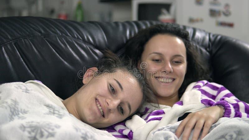 Familj i pijamas som skrattar, medan hålla ögonen på television tillsammans royaltyfria foton