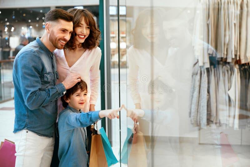Familj i shoppinggalleria Folk som ser till och med fönster royaltyfri foto