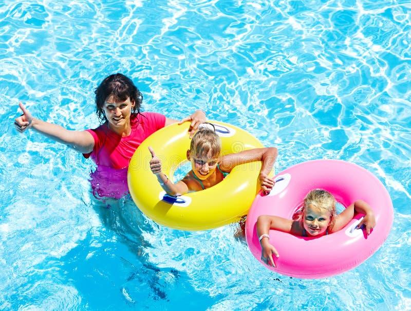 Familj i simbassäng. royaltyfria foton