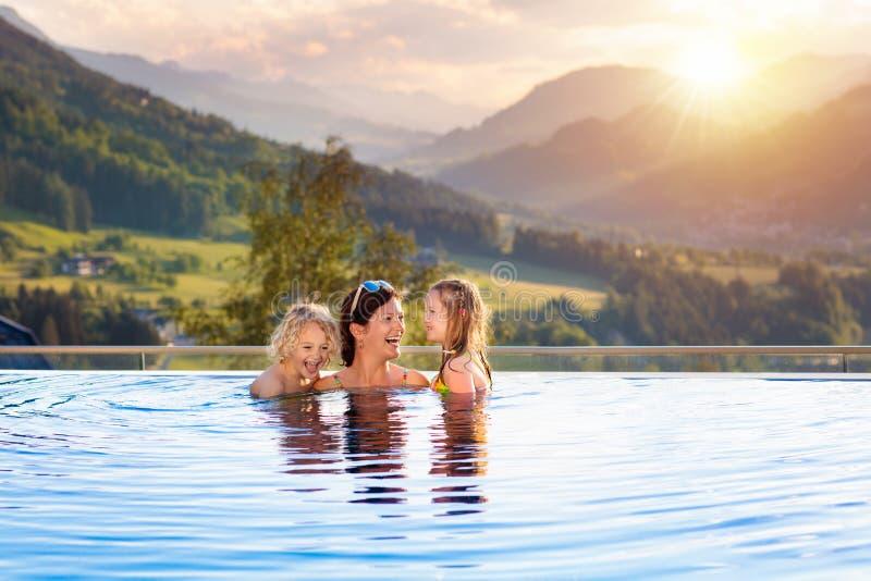 Familj i simbassäng med bergsikt fotografering för bildbyråer