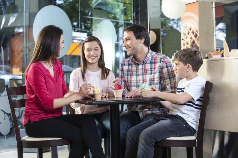 Familj i tillfälligt ha glassar i mottagningsrum royaltyfri bild