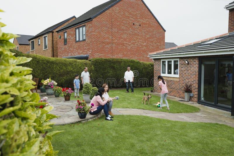 Familj i trädgården i sommar royaltyfri bild