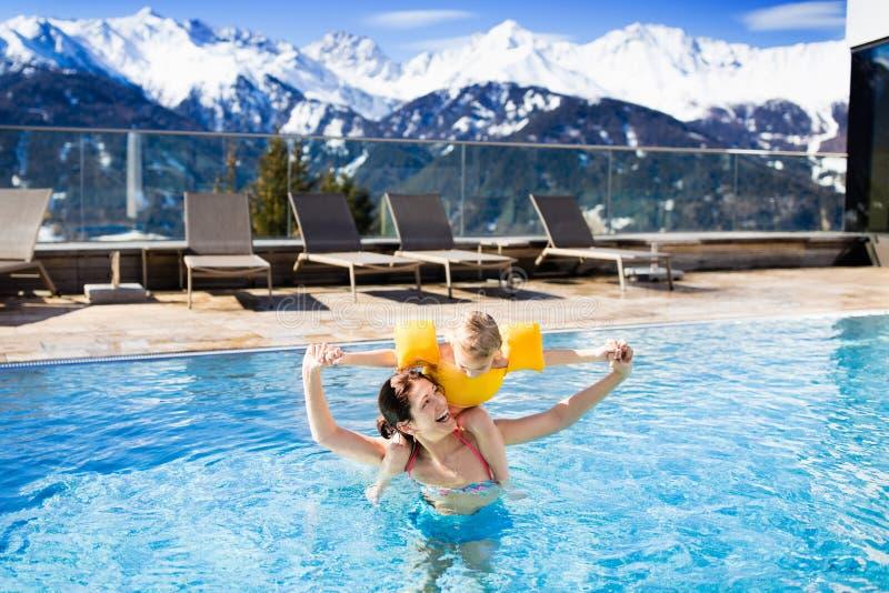 Familj i utomhus- simbassäng av den alpina brunnsortsemesterorten fotografering för bildbyråer