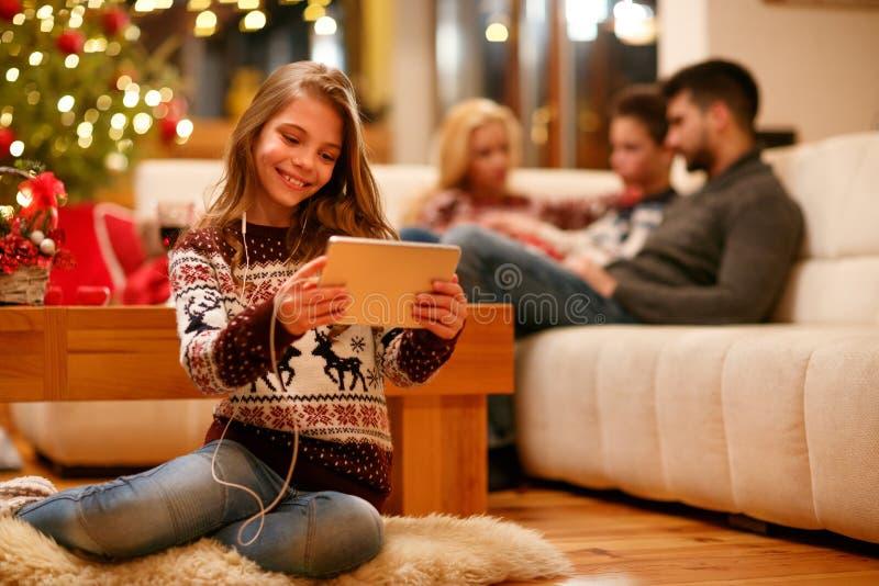 Familj jul, teknologi, musikbegrepp - liten flicka med arkivbild
