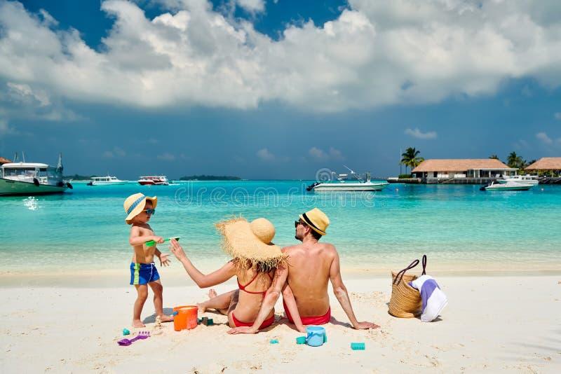 Familj med årig pojke tre på stranden fotografering för bildbyråer