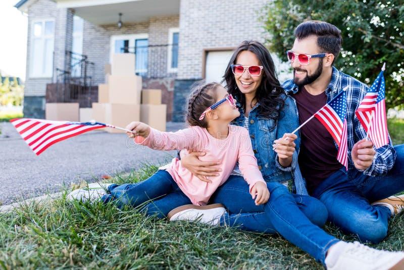 familj med amerikanska flaggan och solglasögon som sitter i trädgård av fotografering för bildbyråer