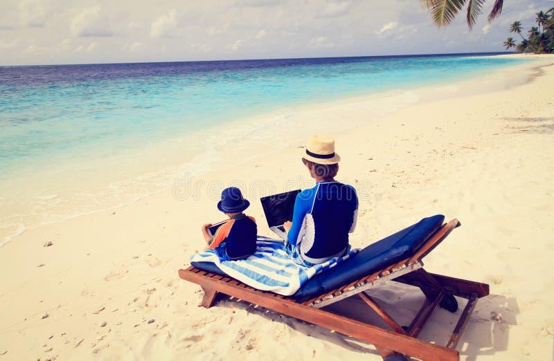 Familj med bärbara datorn och handlagblocket på stranden fotografering för bildbyråer