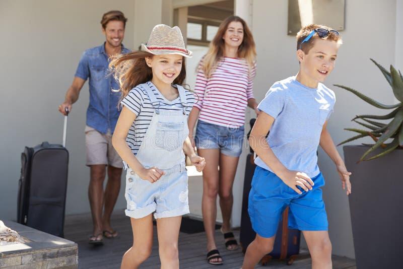 Familj med bagage som lämnar huset för semester arkivfoton