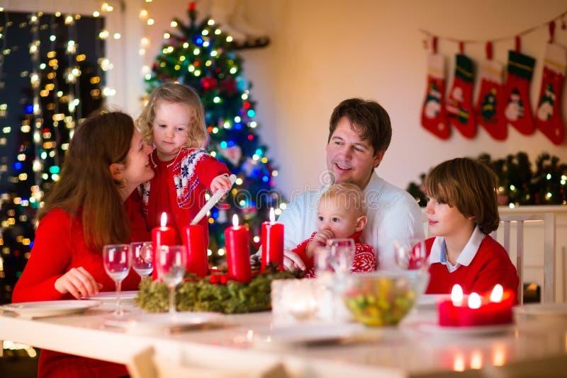 Familj med barn på julmatställen hemma royaltyfri fotografi