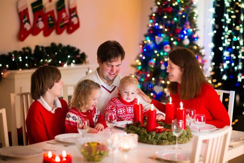 Familj med barn på julmatställen hemma royaltyfri bild