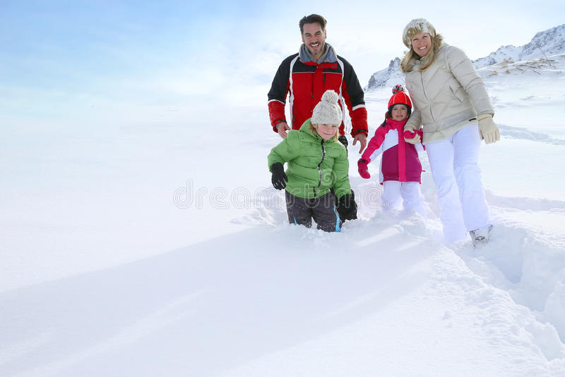 Familj med barn som går i djup snö arkivbilder