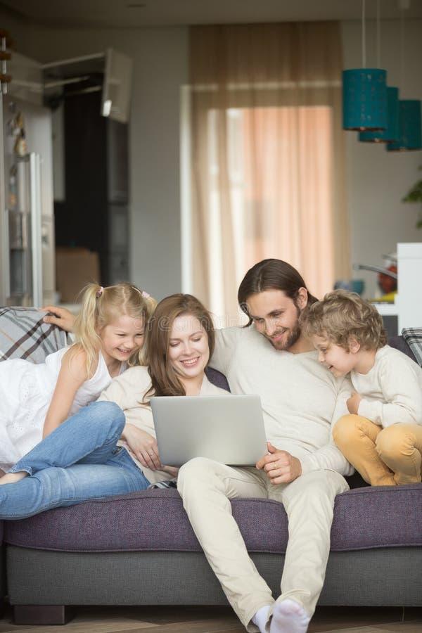Familj med barn som har den roliga användande bärbara datorn på soffan, lodlinje royaltyfri fotografi