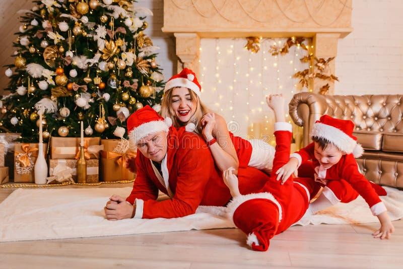 Familj med barn som har gyckel under julgranen arkivfoton