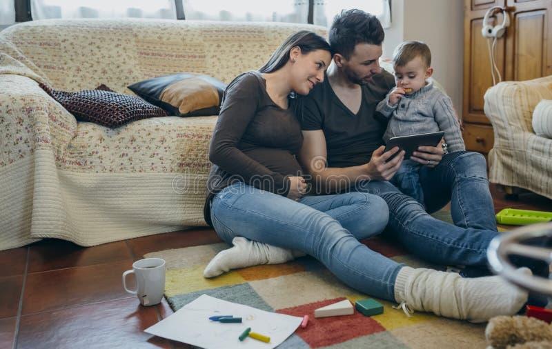Familj med barnet och den gravida modern som ser minnestavlan royaltyfri bild