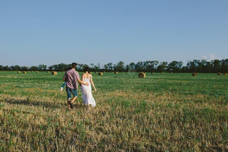 Familj med barnet som går på fältet arkivfoton