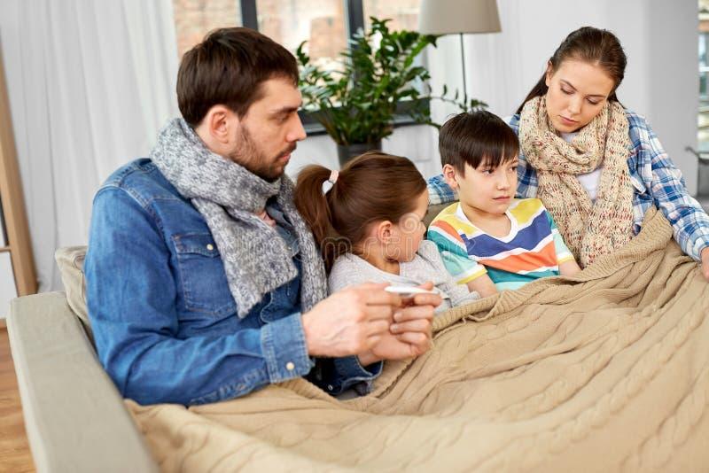 Familj med d?ligt barn som har feber hemma fotografering för bildbyråer