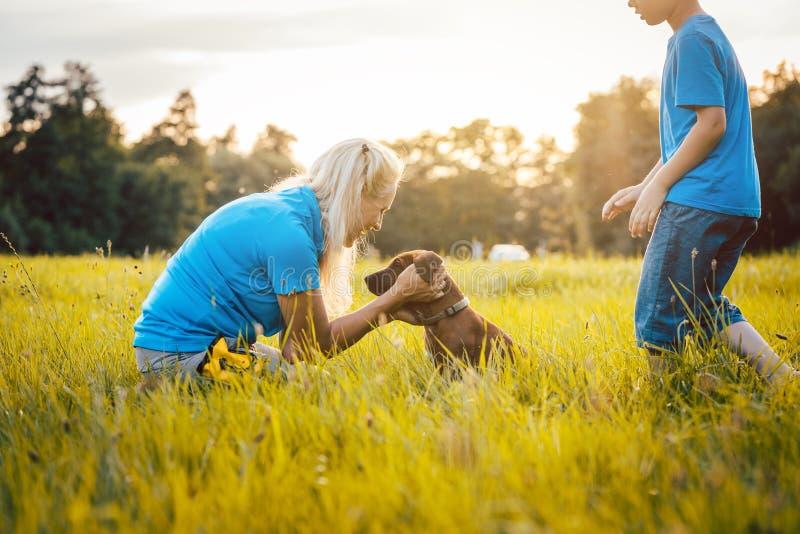Familj med deras hund i natur royaltyfri bild