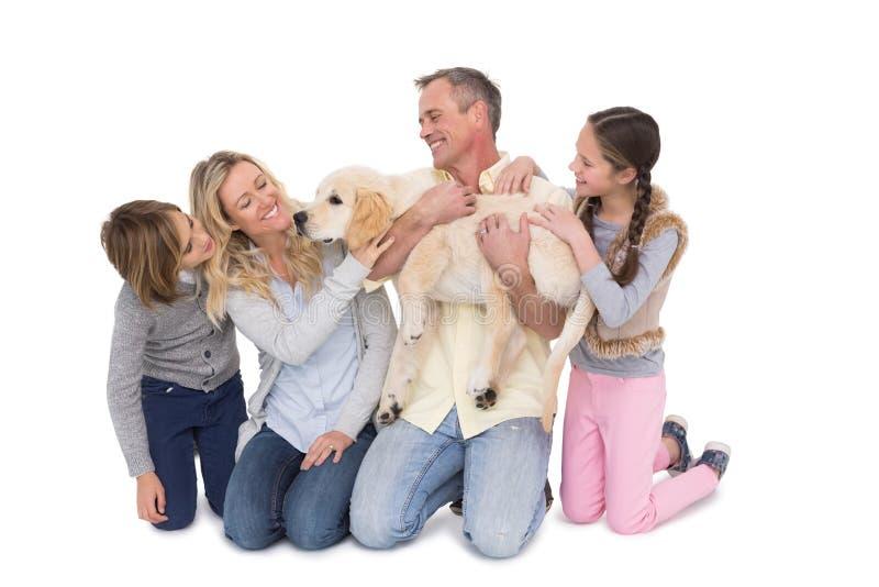 Familj med deras hund som tillsammans poserar och ler på kameran royaltyfri fotografi