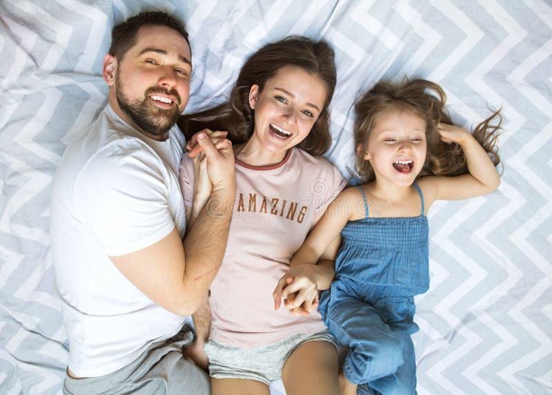 Familj med dottern som har roligt hemmastatt, begreppet av ett lyckligt arkivbilder