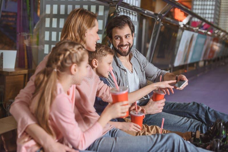 familj med drinkar som vilar, når att ha åkt skridskor royaltyfria bilder