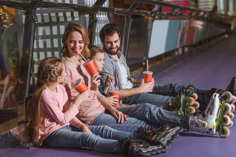 familj med drinkar som vilar, når att ha åkt skridskor royaltyfri foto