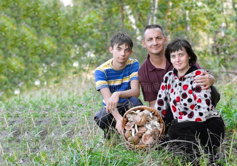 Familj med en korg av champinjoner royaltyfria bilder