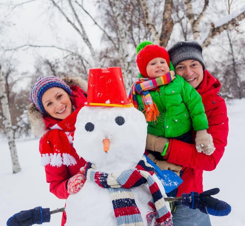 Familj med en snögubbe arkivbild