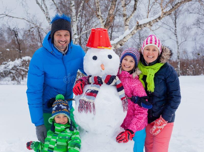Familj med en snögubbe arkivbilder