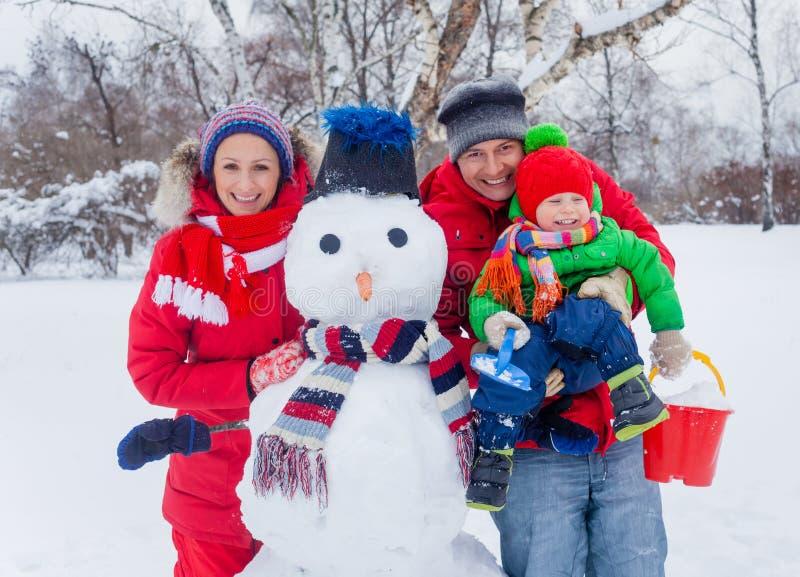 Familj med en snögubbe royaltyfria foton