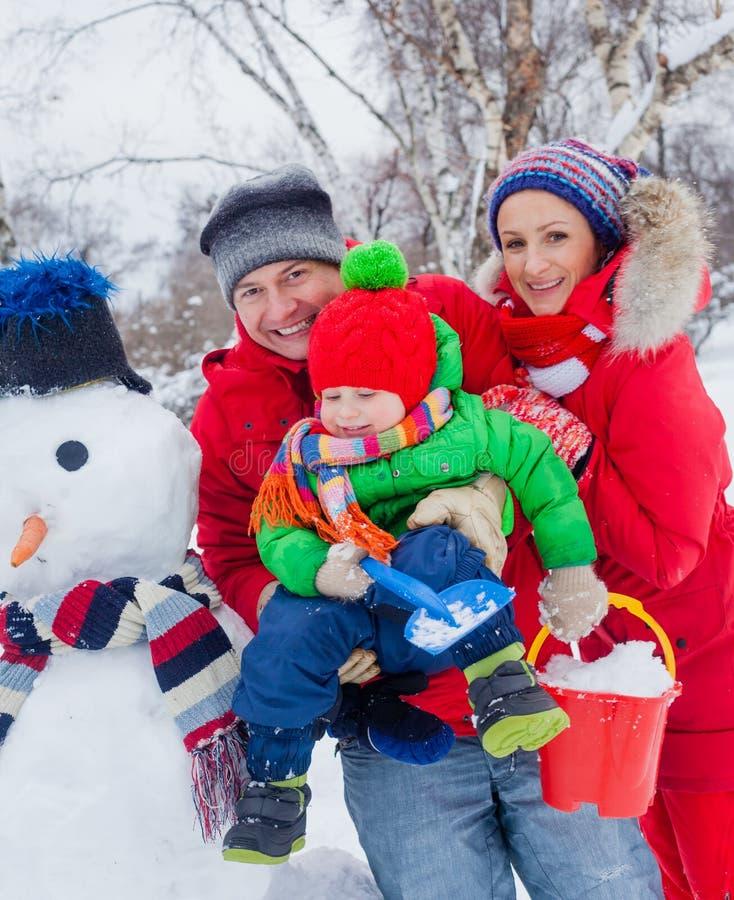 Familj med en snögubbe fotografering för bildbyråer