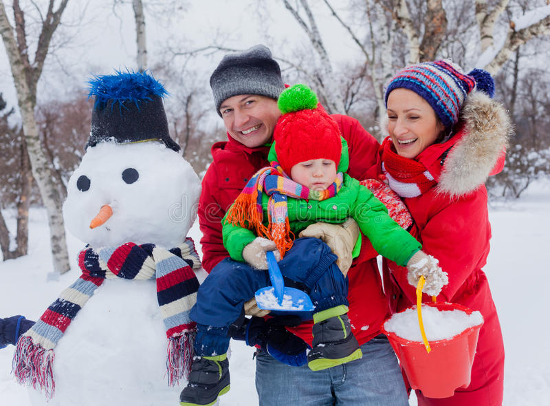 Familj med en snögubbe arkivfoton