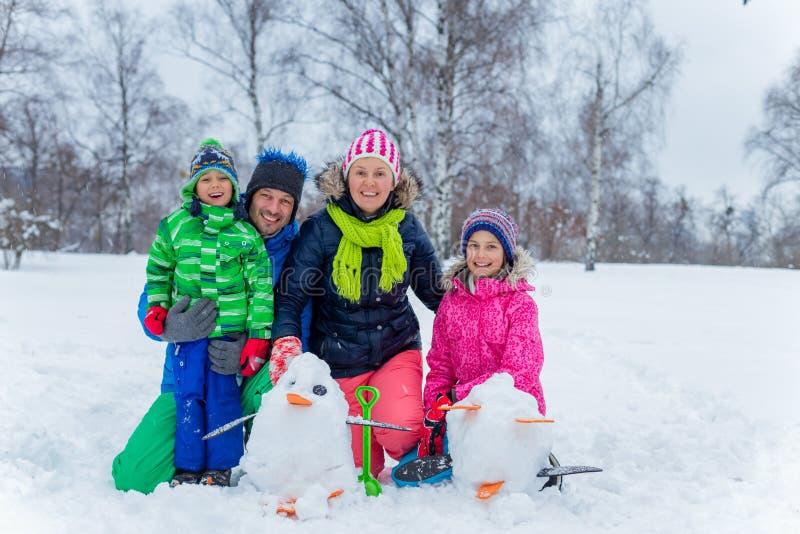 Familj med en snögubbe royaltyfria bilder