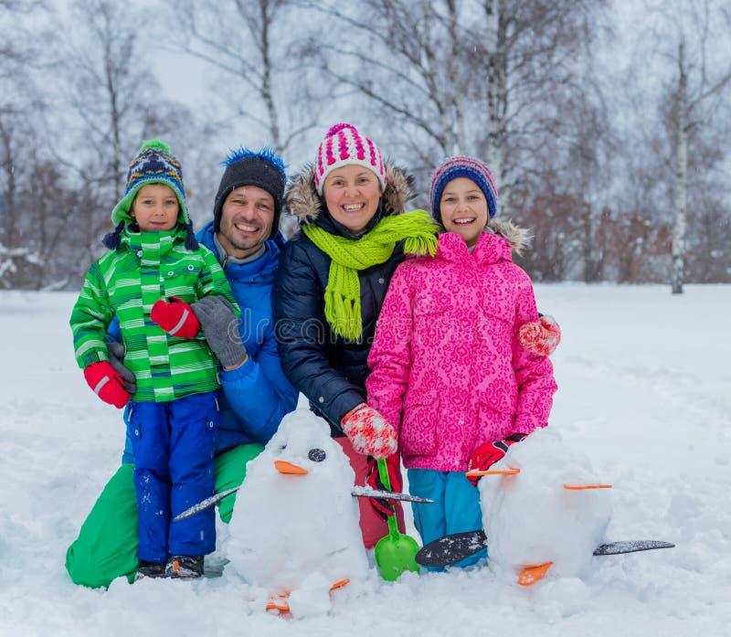 Familj med en snögubbe royaltyfri foto