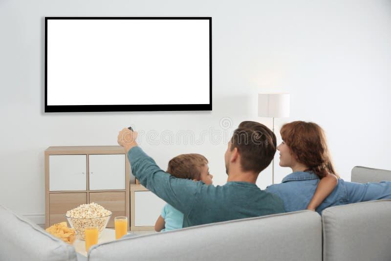Familj med fjärrkontroll som hemma sitter på soffan och hållande ögonen på TV, utrymme för design på skärmen royaltyfri fotografi