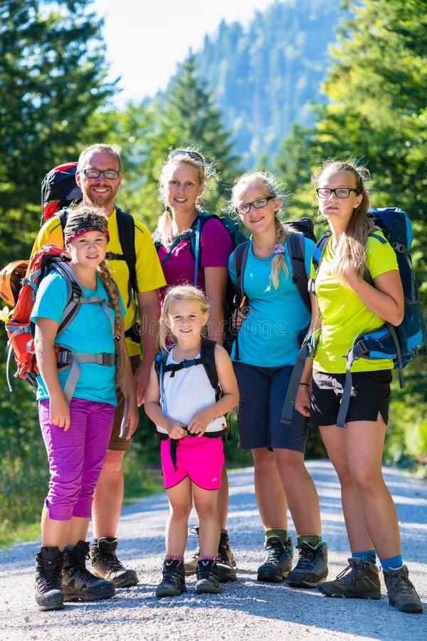 Familj med fyra ungar som fotvandrar i bergen royaltyfria bilder