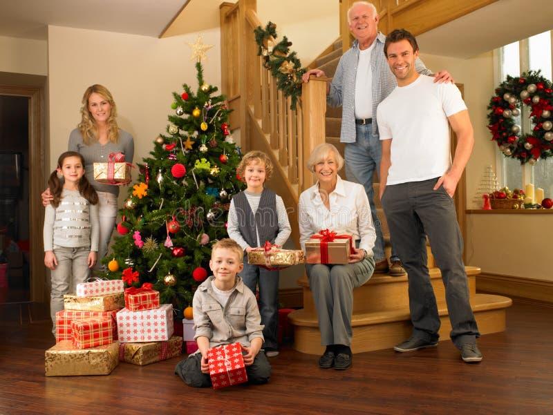 Familj med gåvor runt om julgranen royaltyfri fotografi