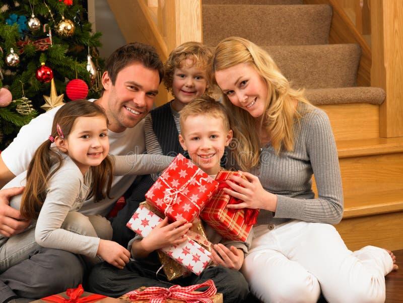 Familj med gåvor som är främre av julgran royaltyfria foton