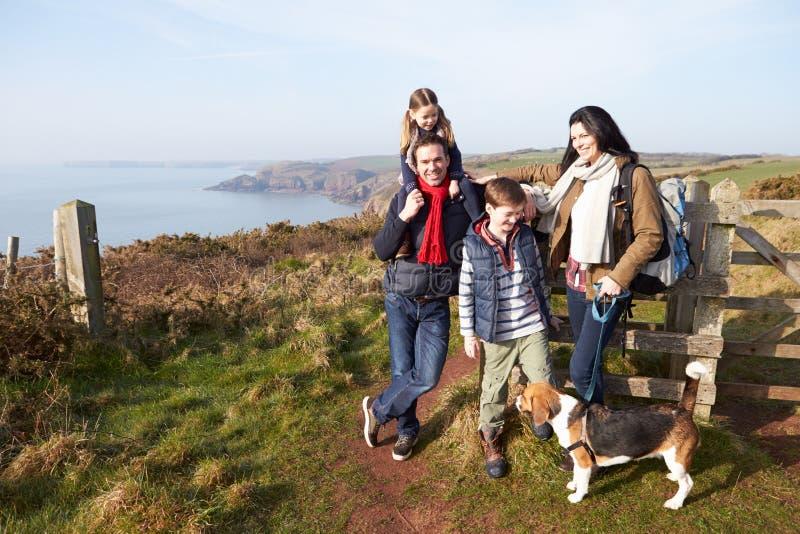 Familj med hunden som promenerar den kust- banan arkivfoton