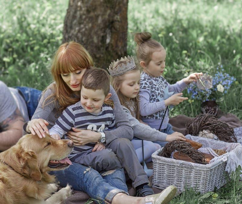 Familj med husdjuret som vilar på gräsmattan arkivfoton