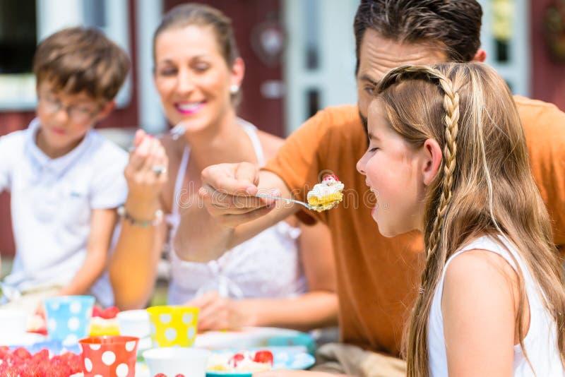 Familj med kakan i sommarträdgård arkivbilder